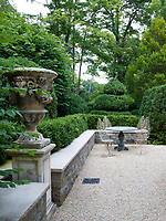 A 1930s French marble table, circa-1900 garden chairs and an antique limestone urn on a terrace.