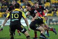 TJ Perenara tries to stop George Bridge during the Super Rugby match between the Hurricanes and Crusaders at Westpac Stadium in Wellington, New Zealand on Saturday, 15 July 2017. Photo: Dave Lintott / lintottphoto.co.nz