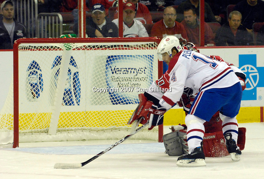 Carolina Hurricanes' goalie Cam Ward can't stop the Montreal Canadiens' Tomas Plekanec, in white, as he scores during the first period Friday, Oct. 26, 2007 in Raleigh, NC. The Canadiens won 7-4.