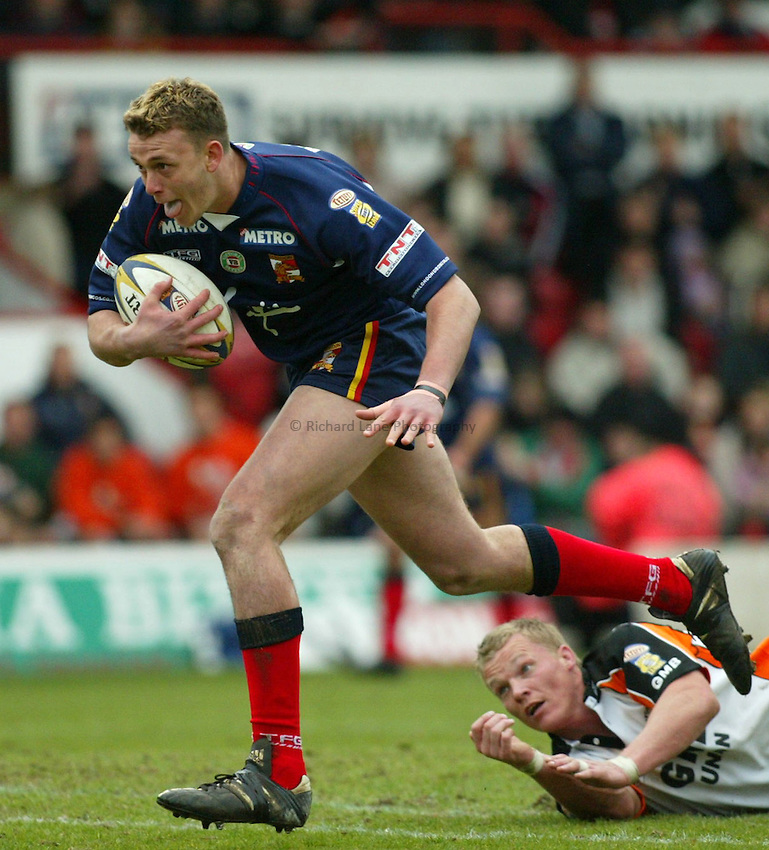 Photo: Scott Heavey.London Broncos V Castleford Tigers..06/04/03..Damien Kennedy of the London Broncos (left) evades a tackle from Lee Harland during this Tetley's Super League VIII R5 match..