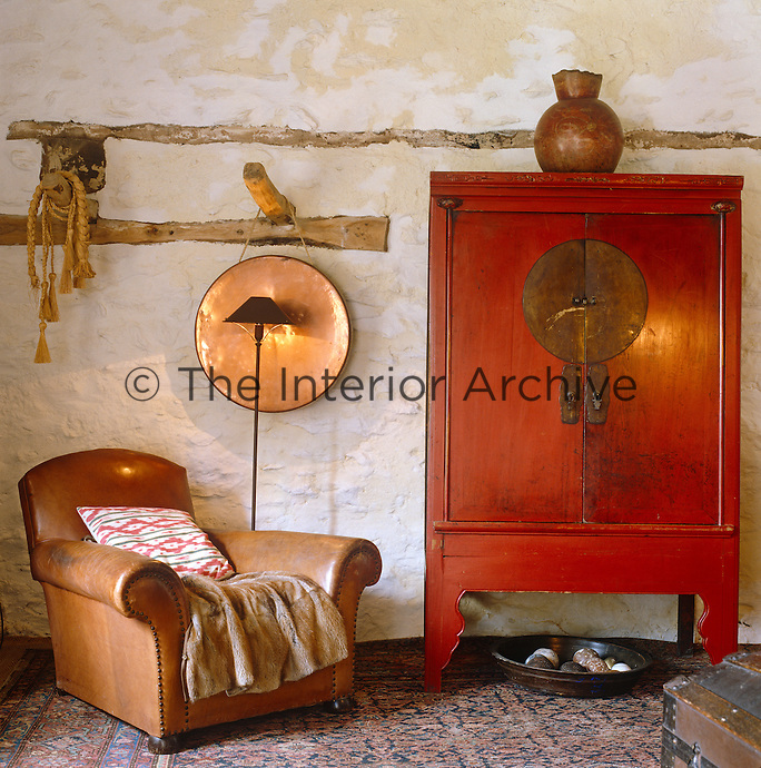 Detail of an old leather armchair and a hand-painted red Chinese cupboard against a white stone wall in the bedroom