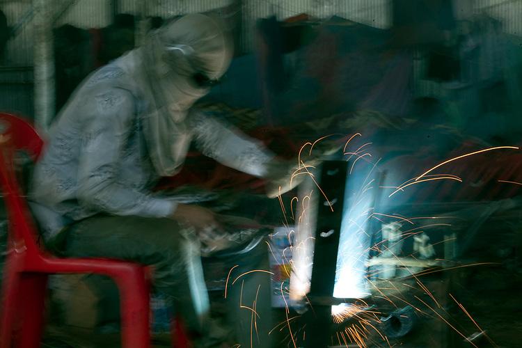 Welder at work in a small workshop in Battambang, Cambodia. <br /> <br /> Photos &copy; Dennis Drenner 2013.