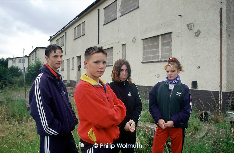 "Teenagers pass the time outside boarded up and empty houses on an estate in Distington, Cumbria which suffers from ""low demand"" as a result of high local unemployment."