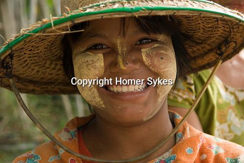Teen girl wearing makeup Thanakha. A natural product, naturally produced. Myanmar Myanma Burma 2011.
