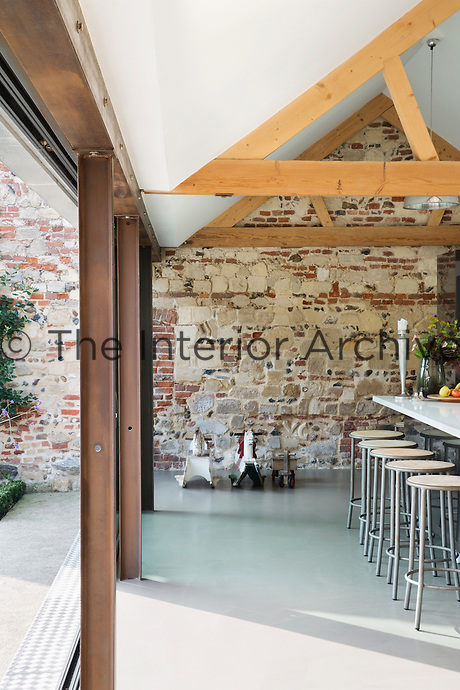 The kitchen sits within an open-plan space with large windows to the front and back. The original stone and brick walls of the barn have been kept exposed and adds a lovely texture to the room.