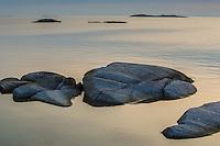 Klippa vid  spegelblankt stilla Kallskär i Stockholms skärgård vid havet.