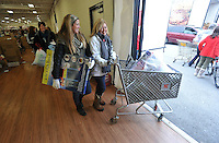 NWA Media/Michael Woods --12/17/2014-- w @NWAMICHAELW...Macy Bodishbaugh (left) and Margo Bodishbaugh help carry out a basket full of toys Wednesday morning to a family at the Salvation Army building in Springdale.  Several volunteers helped distribute toys and food to local families for the holidays.