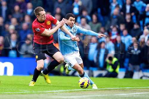 09.12.2012 Manchester, England. Manchester City's Argentinean forward Carlos Tévez and Manchester United's English defender Phil Jones in action during the Premier League game between Manchester City and Manchester United from the Etihad Stadium. Manchester United scored a late winner to take the game 2-3.