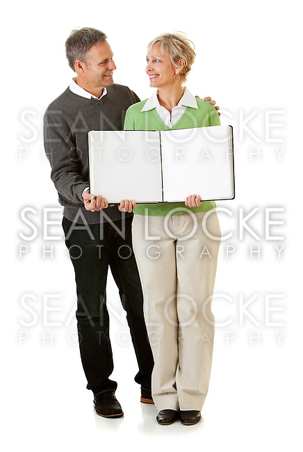 Series with a mature couple, mid 50's, in various themes, including healthy eating, medical and fun.  Isolated on white and an interior room.  Holding an open scrapbook.