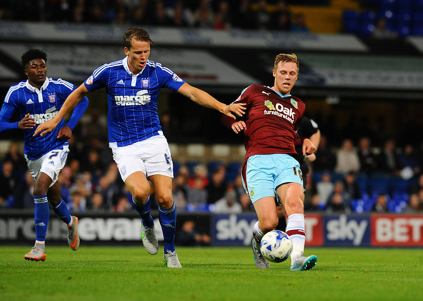 Burnley's Rouwen Hennings plays the ball forward under pressure from Ipswich Town's Christophe Berra<br /> <br /> Photographer Ashley Pickering/CameraSport<br /> <br /> Football - The Football League Sky Bet Championship - Ipswich Town v Burnley - Tuesday 18th August 2015 - Portman Road - Ipswich<br /> <br /> &copy; CameraSport - 43 Linden Ave. Countesthorpe. Leicester. England. LE8 5PG - Tel: +44 (0) 116 277 4147 - admin@camerasport.com - www.camerasport.com