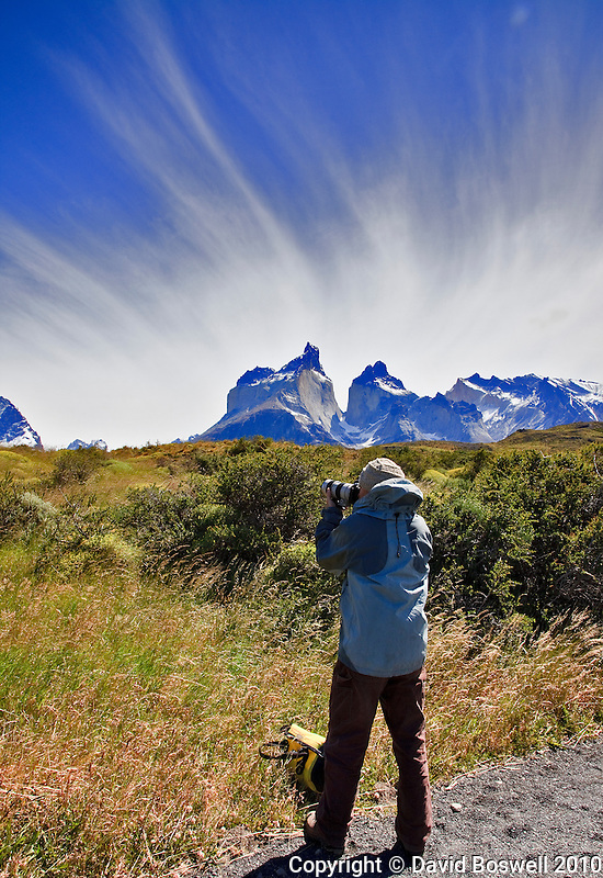 Interesting clouds formations crown The Horns (Los Cuernos) as a photographer photographs Torres del Paine, Chile.