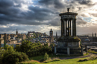 Edinburgh Skyline as viewed from Calton Hill, Edinburgh, Scotland.  .Dugald Stewart Monument (Scottish philosopher) in foreground. Also seen on the skyline, the Scott Monument, the Balmoral Hotel (tower with the clock), the Edinburgh Castle, and the Political Martyrs Obelisk, among others.  .The Calton Hill is one of the more iconic locations in Edinburgh.