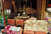 Clignancourt Flea Market shop with brocaded textiles and chairs at open French doors. Ornate sculpted clock, urns and vases. Owner sits inside by elegant table crowded with crystal. Furniture, paintings, tapestry, chinaware, etc. Paris, France.
