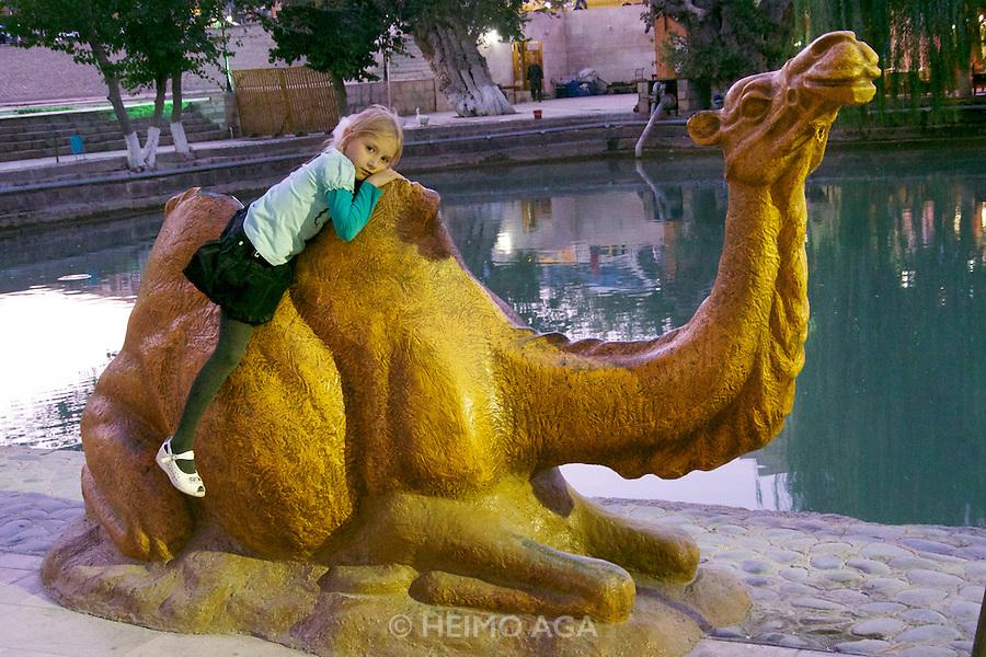 Uzbekistan, Bukhara.<br /> Lyabi-Hauz. Little girl sitting on the Caravan Monument.