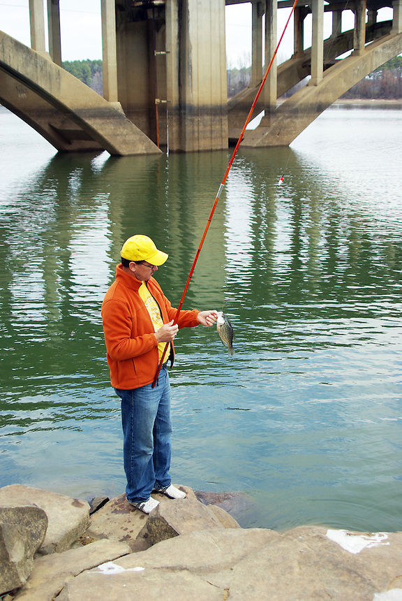 Bank fisherman catching crappie by bridge in Lake Greeson Arkansas