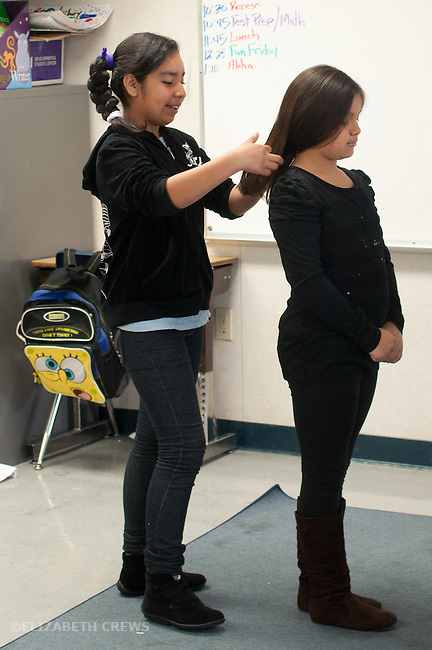 Oakland CA Latina girl in 3rd grade class arranging friend's hair