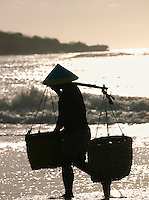 Fisherman carrying baskets along shoreline, Bali, Indonesia.