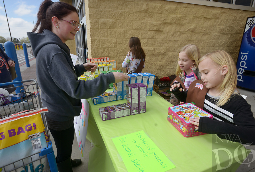 NWA Democrat-Gazette/BEN GOFF @NWABENGOFF<br /> Janell Taylor (from left) of Elm Springs buys Girl Scout Cookies from Caroline Barnett, 9, and Olivia Tingley, 8, Saturday, March 12, 2017, while Girl Scout Brownie Troop 5343 holds a sale outside the Wal-Mart on Elm Springs Road in Springdale. The troop plans to donate $200 from the sale to the Springdale Animal Shelter and was also accepting donations to give cookies to the Springdale Police Department.