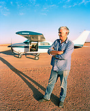 AUSTRALIA, the Outback, Pilot Trevor Wright standing next to his airplane