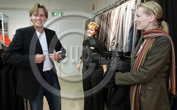 ROERMOND - NETHERLANDS - 01 DECEMBER 2006 -- Daniel (Le) came to shop in the Designer Outlet Roermond from Germany with his sister Christina (Ri). Here he is trying out a blazer in the Boss shop with the assistance of a sales lady. -- Developed, owned and operated by McArthurGlen, the Designer Outlet Roermond is the leading designer outlet in Europe. It has 2.5 million visitors each year and 20.1 million people live within 90 minutes drive from it. -- PHOTO:  JUHA ROININEN / EUP-IMAGES