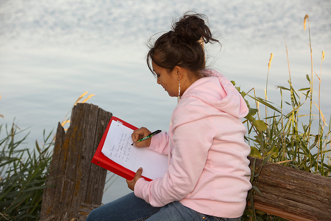 Native American teenager writes a letter on notebook. Could also be doing homework while in an outdoor setting