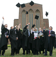 Happy graduates celebrate by tossing their mortarboards in the air, University of Surrey.