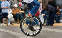 A unicyclist makes his way through downtown during the Miles City Bucking Horse Sale parade in Miles City, Montana Sat., May 19, 2007.