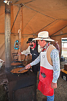 In October, the 22nd Annual Lincoln County Cowboy Symposium brought together  chuckwagon crews and cooks from ranches all over the southwest to compete in preparing food for a hungry crowd. Copdy Perkins from the Calk Chuck Wagon stirs the chicken fried steak.