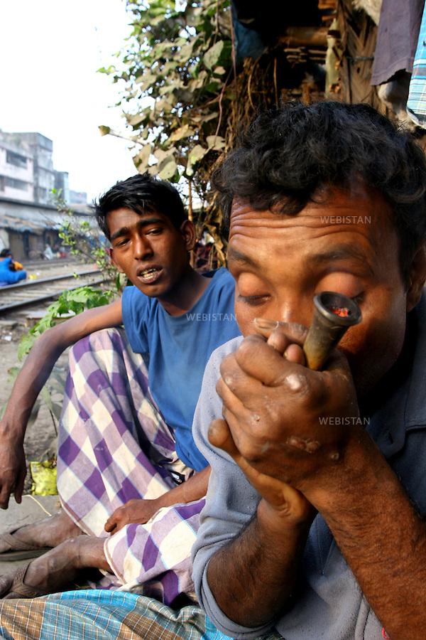 2006. Bangladesh, Dhaka. Marijuana users in a slum. .Marijuana is still the most popular addictive substance in widespread use in Bangladesh but the marijuana smoked today is said to be 15 times more potent than that smoked in the 60s. The result is that those who smoke it have significantly more respiratory symptoms like chronic cough and mucus production, wheezing, and acute bronchitis, than previously..2006. Bangladesh, Dhaka. Consommateur de marijuana dans un bidonville. .La marijuana est encore la substance additive la plus populaire de grande consommation au Bangladesh, mais on dit que la marijuana fumée aujourd'hui est dix fois plus puissante que celle fumée dans les années 60. Par conséquent ceux qui la fument ont beaucoup plus de troubles respiratoire comme par exemple des toux chroniques et production de mucus, des poumons sifflant et des bronchites aigues qu'avant..