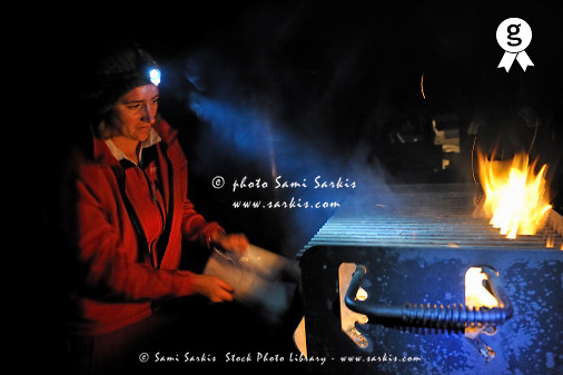 Woman flaming barbecue coals at night (Licence this image exclusively with Getty: http://www.gettyimages.com/detail/85071263 )