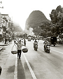 CHINA, Guilin, people work, walk and ride motorbikes on the streets of Guilin (B&W)