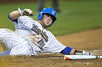 UCLA second baseman Cody Regis (18) slides across the plate against the Mississippi State Bulldogs during the 2013 Men's College World Series Final on June 25, 2013 at TD Ameritrade Park in Omaha, Nebraska. The Bruins defeated the Bulldogs 8-0, winning the National Championship. (Andrew Woolley/Four Seam Images)
