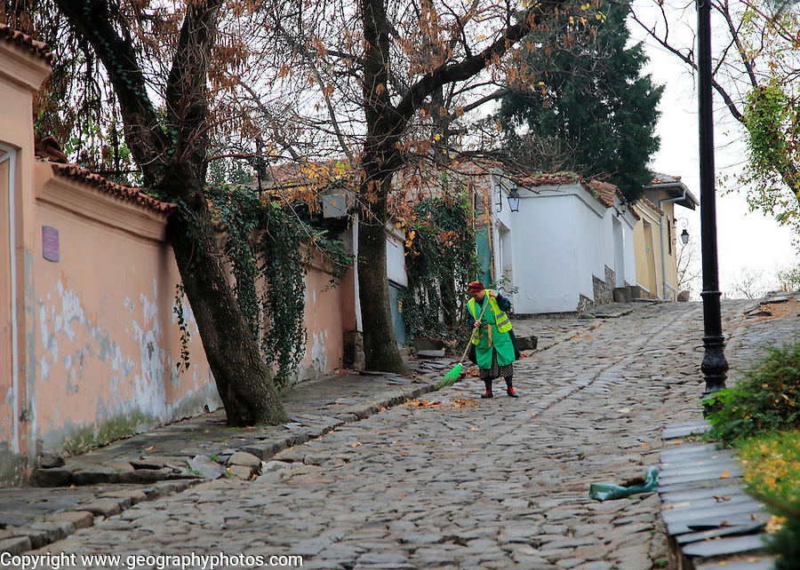Woman sweeping cobbled street in old town of Plovdiv, Bulgaria, eastern Europe