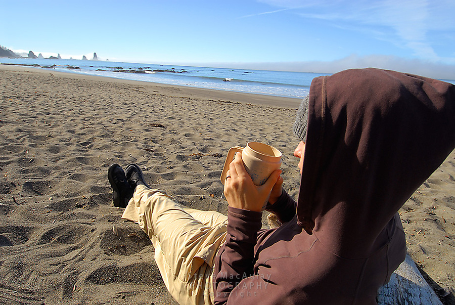Woman in brown hoodie drinking coffee on beach, Olympic National Park, Coastal Strip, Olympic National Park, WA.