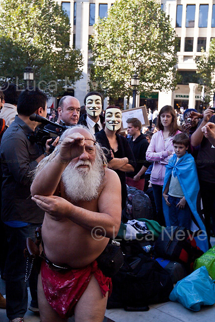 """London, 15/10/2011. St Paul's Square became the stage of the UK arm of the """"Occupy"""" protest movement which has been growing around the world. The Occupy movement is a world-wide protest against the financial crises created by the actual financial system, by speculation, by deregulation, and by the actions of major international financial and investment banks. Around 2,000 protesters armed with tents and placards, gathered outside the famous Cathedral intending to occupy Paternoster Square, home of the London Stock Exchange and the heart of the City of London, but they were hampered by City police officers. After this failed attempt the protesters decided to camp in front St Paul's where the situation with police forces became immediately tense. Masked like the character of Guy Fawkes from the movie """"V for Vendetta"""", Julian Assange appeared on the square to give a speech in support of the protesters. During the late evening police forces heavily armed with riot control equipment charged the square, attempting to evict the occupants who resisted. Later in the evening the police retreated and the occupation continued peacefully."""
