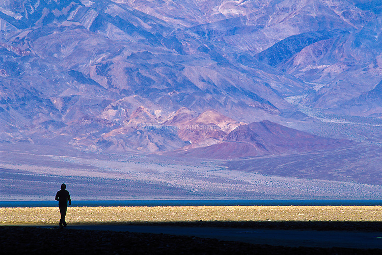 Visitor takes a walk at Badwater, lowest point in North America El.  282 ft (86 m) below sea level. Badwater Basin is an endorheic basin (no  outflow). Average annual precipitation is 1.58 inches (40 mm). Base of Panamint Mountains in background. Death Valley National Monument Est. February 11, 1933; Death Valley National Park in 1994. 5,270 square miles (13,649 km2). Inyo County, CA.