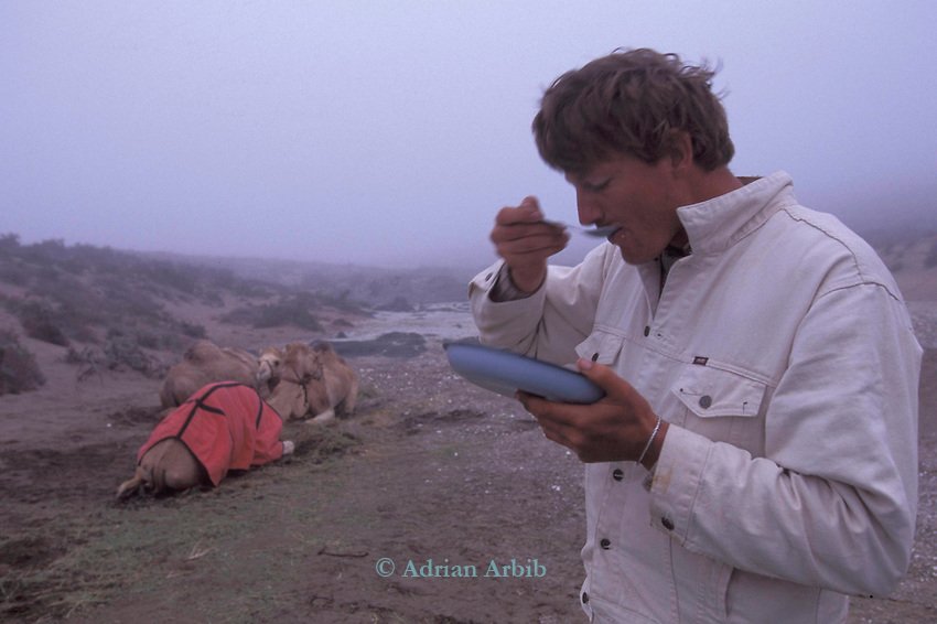 Benedict Allen  eating breakfast as an early sea mist moves in, during his journey through the  restricted  Diamond mining region of the  Namib Naukluft  desert as he travelled  from South Africa to Angola, 1,700 miles. Skeleton Coast, Namibia..
