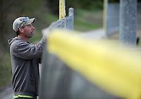 NWA Democrat-Gazette/ANDY SHUPE<br /> William Graham, Parks and Recreation foreman for the city of Prairie Grove, reattaches windscreen Wednesday, March 23, 2016, to the outfield fence at one of the ball fields at Delford Rieff Park in Prairie Grove. High winds had pulled portions of the screen down, so Graham and a helper, Scott Kinion, were reattaching it in preparation for the upcoming season.