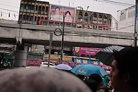 Semblant reagrder l'autoroute qui traverse Bangkokg le couple royal veille sur les passants dans le quartier très fréquenté de Ratchaprasong, sous les pluies d'août.