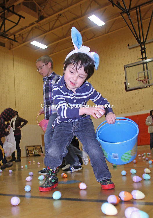 Winsted, CT-032313MK13  Dominic Sogliuzzi puts an egg into his baskets as he eyes another to gather during the annual easter egg hunt at Person Middle School in Winsted on Saturday morning.  Tricia Twomuy, parks and recreation director, said that volunteers placed 1500 eggs for the activity.  Approximately 150 children participated in two different aged group hunts.  One was for toddlers to four years and one for five to eight year olds. Michael Kabelka Republican American