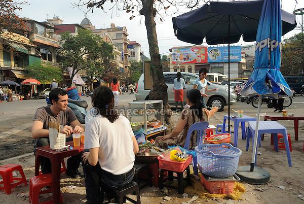Asia, Vietnam, Hanoi. Hanoi old quarter. Tourists having some street food.
