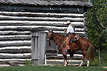 A cowboy and horse next to a log cabin