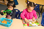 Education preschool 3 year olds two girls sitting side by side, playing separately, one with puzzle and the other looking at onion with magnifying glass