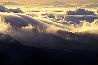 Ethereal clouds swirl at sunrise on the summit of Haleakala (House of the Sun) on the island of Maui.