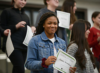 NWA Democrat-Gazette/CHARLIE KAIJO Jamie Woodard (center) holds up a certificate for achieving straight As during an awards assembly, Friday, January 11, 2019 at the Arkansas Arts Academy in Rogers. <br />