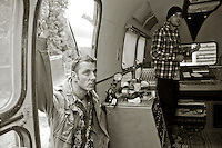 """Musicians listening to a recording just made.  An airstream trailer fitted out as a mobile sound recording engineer's mixing base .  Set up to record the """"Edge of Chaos Orchestra"""" playing inside the Blue Coconut Club, Pulborough, West Sussex."""