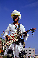 Electric guitar player with turban and rollar skates in Venice, Los Angeles, California, USA