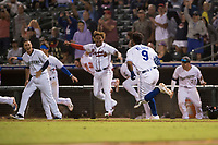 AFL West catcher Meibrys Viloria (9), of the Surprise Saguaros and Kansas City Royals organization, sprints towards first base after hitting a walk-off line drive to center field as his teammates, including Evan White (15), Cristian Pache (27) and Keston Hiura (23), charge the field to celebrate the win during the Fall Stars game at Surprise Stadium on November 3, 2018 in Surprise, Arizona. The AFL West defeated the AFL East 7-6 . (Zachary Lucy/Four Seam Images)