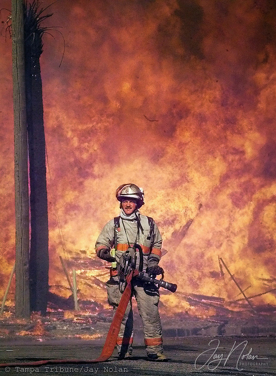 """A firefighter waits for the flow of water as a fire in Ybor City  burns out of control Friday May 19, 2000.  It went up like logs on a bonfire. When flames licked the wooden frames of the apartments in The Park at Ybor City, it touched off a blaze that quickly destroyed the apartment complex and, a short time later, a nearby post office. Firefighters battled the inferno - and their exhaustion - for hours. When it was over, five city blocks were leveled at a cost of about $40 million. ( Ybor City Inferno - Camden Property Trust - Apartments , Six-Alarm Fire )   JAY NOLAN - TRIBUNE PHOTO  (10/06/00 -- The Fire on May 19 was very similar to an Ybor fire 100 years prior.  Both are the subject of a new book, """"Forged in Fire"""".)"""