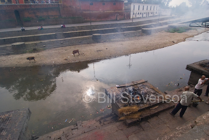 The Bagmati River, considered holy by both Hindus and Buddhists, flows through the city choked almost to a standstill with filth garbage and the remains of the cremated who have been pushed into the holy river. In this picture a cremation is nearly finished, shortly, what remains of the body, will be pushed into the river and from there it will make its journey all the way to the holy Ganges.